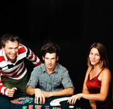 Young people playing poker on black background Royalty Free Stock Photos