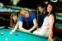 Young people playing pool Royalty Free Stock Photos