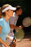 Young people playing tennis. Mixed doubles, side view Royalty Free Stock Photos