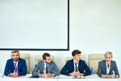 Young People in political Debate. Portrait of several business people sitting in row participating in political debate during press conference answering media royalty free stock images