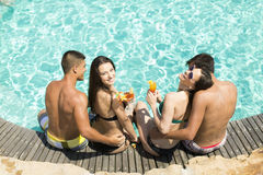 Young people by the pool. Young people relaxing by the pool at sunny day Royalty Free Stock Photo