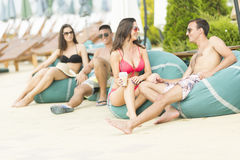 Young people by the pool. Young people relaxing by the pool at sunny day Stock Images