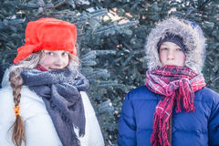 Young people portrait in warm clothes in frosty winter day during Christmas holidays in forest among blue fir trees Royalty Free Stock Photo