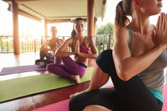 Young people practicing yoga in spinal twist pose Stock Image