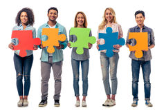 Young people with puzzles. Young people of different nationalities with colorful pieces of puzzle are looking at camera and smiling, isolated on white background Stock Image