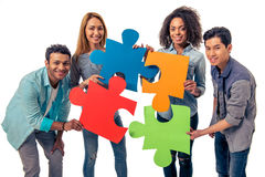 Young people with puzzles. Young people of different nationalities with colorful pieces of puzzle are looking at camera and smiling, isolated on white background Royalty Free Stock Photo