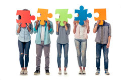 Young people with puzzles. Young people of different nationalities are hiding faces behind colorful pieces of puzzle, isolated on white background Stock Images