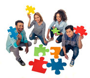 Young people with puzzles. High angle view of young people of different nationalities with colorful pieces of puzzle looking at camera and smiling, on white Stock Photo
