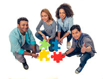 Young people with puzzles. High angle view of young people of different nationalities with colorful pieces of puzzle looking at camera and smiling, on white Stock Image