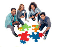 Young people with puzzles. High angle view of young people of different nationalities with colorful pieces of puzzle showing Ok sign and smiling, on white Stock Image