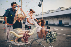 Young people racing with shopping cart and celebrating with conf. Multiethnic young people racing with shopping cart. Young friends having fun on a shopping Stock Image