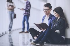 Young People are Reading Book in the Hall. Happy Students at College. Education and Career Concept. Studying in University. Funny Students. Laughing Team of stock photography