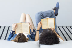 Young people reading book. In home Royalty Free Stock Photo