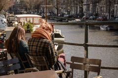 Young people reading books in an outdoor café along a canal in Amsterdam Netherlands. March 2015. Landscape format royalty free stock photography