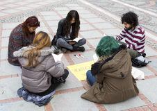 Young people reading street. Istanbul, Turkey - November 16, 2014: Young people are reading books and painting on a street in Istanbul Royalty Free Stock Photos