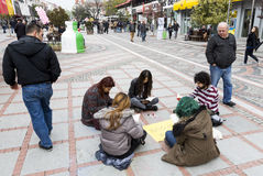 Young people reading street. Istanbul, Turkey - November 16, 2014: Young people are reading books and painting on a street in Istanbul Royalty Free Stock Photo