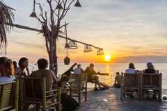 Young people relax in an outdoor bar on a cliff in the sunset Royalty Free Stock Photos