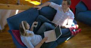 Young people relaxing with music at home. High angle shot of young man and woman relaxing and dancing with music lying on the sofa at home. Woman wearing stock video footage