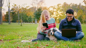 Young people relaxing in a park. Asian man uses a laptop, woman reading something on a tablet stock footage