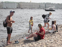 Young people relaxing in a Sunny day on the banks of the river Neva in Saint-Petersburg. Russia. The summer of 2017. Stock Image