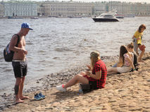 Young people relaxing in a Sunny day on the banks of the river Neva in Saint-Petersburg. Russia. The summer of 2017. Royalty Free Stock Photography