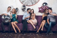 Young people rest in pairs in a nightclub. They drink champagne and sing songs. Royalty Free Stock Images