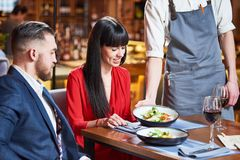 Restaurant service. young couple and waiter with salad plates Royalty Free Stock Image