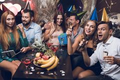 Young people are resting in a trendy nightclub. A guy in a white shirt and a girl in a black dress are singing. They have glasses with champagne in their hands Stock Photography
