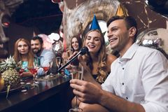 Young people are resting in a trendy nightclub. A guy in a white shirt and a girl in a black dress are singing. They have glasses with champagne in their hands Royalty Free Stock Photos