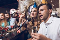 Young people are resting in a trendy nightclub. A guy in a white shirt and a girl in a black dress are singing. They have glasses with champagne in their hands Stock Photo