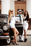 Young people with a retro car. Stock Images