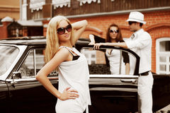 Young people with a retro car. Stock Image