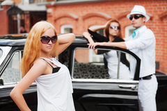 Young fashion people at the retro car Stock Photos