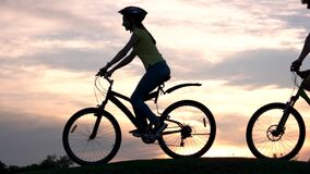 Young people riding bicycles at sunset. stock video