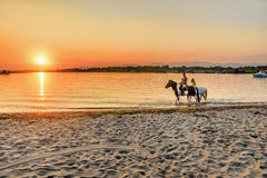 Young people riding horses in the sunset by the sea on the islan Stock Photo