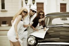 Young fashion people with road map next a retro car Royalty Free Stock Images