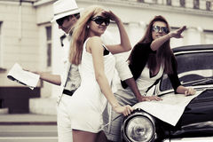 Young people with a road map at the retro car Royalty Free Stock Images