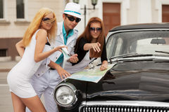 Young tourists with a road map at the retro car Stock Images