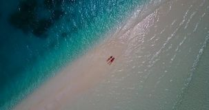 2 young people romantic couple sunbathing with drone aerial flying view on a beach with white sand and beautiful Royalty Free Stock Photo