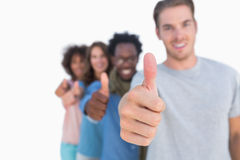 Young people in row with thumbs up Royalty Free Stock Image