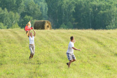 Young people run on meadow flying kite. Happy couple men and women outdoors fly a kite royalty free stock images