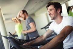 Young people running on a treadmill in health club. stock image