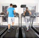 Young people running on treadmills. In gym Stock Images