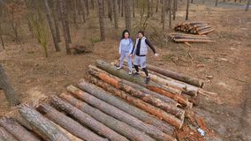 Young people runs on the logs in the forest. Young sport people makes morning exercises outdoors. Pretty woman and handsome man wearing sportswear training in stock video footage
