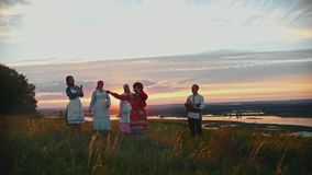 Young people in russian traditional clothes having fun on the field on a background of beautiful sunset - a man playing. Balalaika and women dancing by the stock video