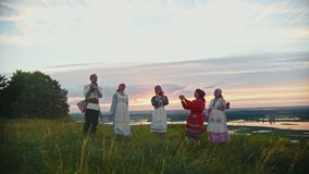 Young people in russian traditional clothes having fun on the field - dancing and clapping their hands. Mid shot stock video