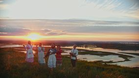 Young people in russian traditional clothes standing on the field on a background of beautiful sunset and singing. Mid shot stock video