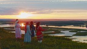 Young people in russian traditional clothes standing on the field and enjoying the view on sunset - river and little. Islands. Mid shot stock video