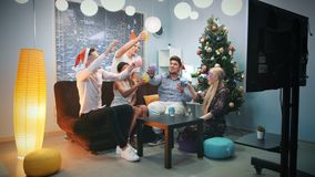 Young people in Santa hats and party masks making cheers on Christmas. They celebrate holiday at home near the Christmas tree stock footage