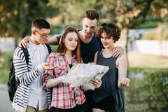 Young people searching the location on map,. People travel, vacation, holidays, friendship, student exchange program. Young people searching the location on map Royalty Free Stock Images